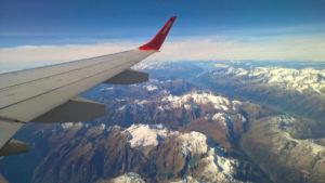 Photo prise d'un avion en vol. Ciel est bleu, quelques nuages blancs. Le spectacle est grandiose au dessus de chaînes de montagnes enneigées. Du blanc, du bleu, un bout d'aile rouge.