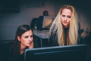 Deux femmes, l'une assise et l'autre debout, lisent et réfléchissent en regardant un écran d'ordinateur. Elles sont concentrées En arrière-plan, un collègue travaille. Ambiance studieuse et feutrée. Peu de lumière.