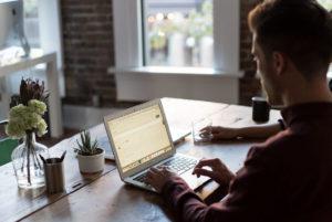 un homme assis à une table travaille sur son ordinateur. Quelques plantes ornent sa table. Une fenêtre floue. Le bras d'une femme tenant un verre à la droite de l'homme.