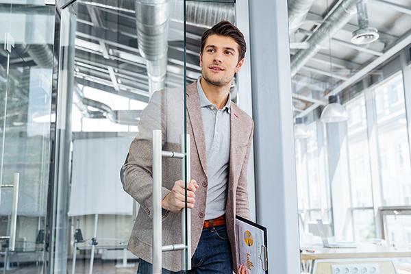 Jeune homme, veste et tenue décontractée sort d'une grande salle vitrée et claire, un document sous le bras. Il pousse la porte et regarde au loin, confiant. Il est décidé.
