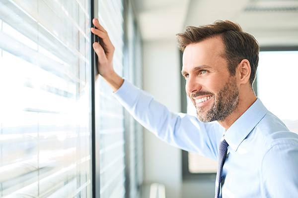 Un homme d'une trentaine d'années, chemise, cravate, grand sourire et dents blanches regarde par la fenêtre la main droite appuyée sur la fermeture métallique. Il regarde vers l'extérieur, très confiant.