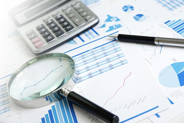 Un plan de travail avec loupe, calculatrice et stylo. Sur la table des documents de travail, des graphiques, des courbes. Un peu de fouillis pour signifier la complexité des calculs.