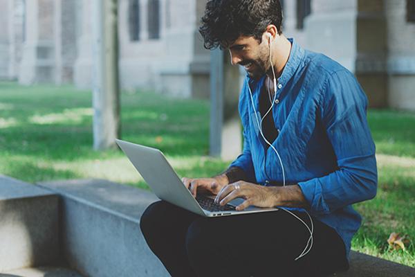 Homme, pantalon noir, chemise bleue, assis sur le muret près d'un parc, une bâtisse en fond ; ordinateur sur les genoux, écouteurs dans les oreilles, ses mains sur le clavier