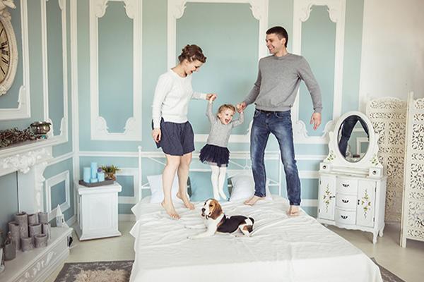 Famille bonheur : père mère, petite fille et chien, tous sautent sur un lit blanc. Une coiffeuse, un paravent, une commode avec des bougies, une cheminée et quelques touches vertes sur les murs.