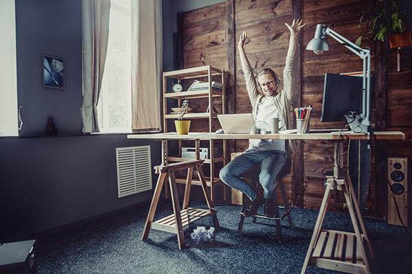 homme assis à un bureau en planche sur tréteaux , pot avec des crayons, mur en bois derrière lui, étagère et baffles. Il lève les bras, casque sur la tête.