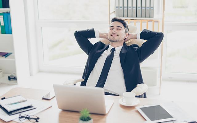 Un jeune homme en costume s'étire dans son fauteuil, les mains derrière la tête, une tasse vide près de son ordinateur. Il a l'air satisfait. L'environnement est clair, seule tâche de couleur, une plante verte.